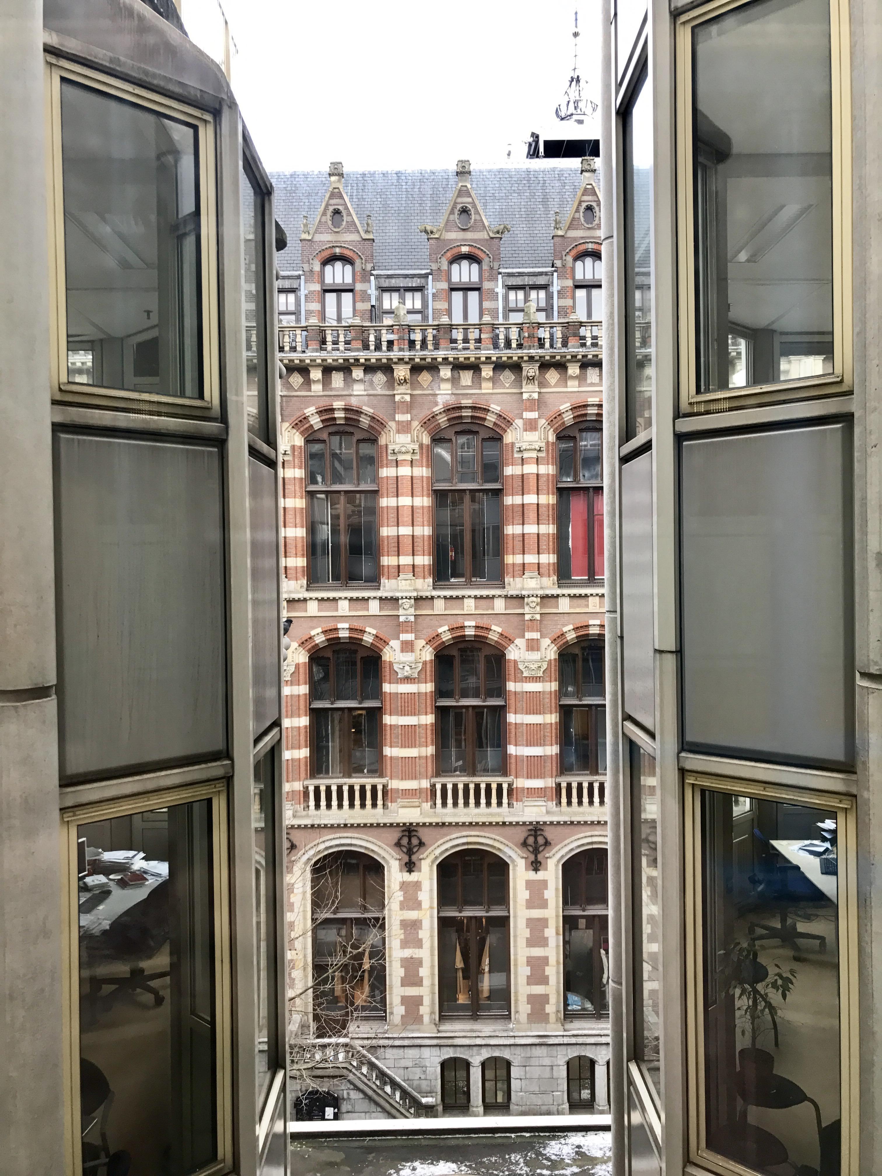 """Utsikten fra universitetskorridoren og over gata til """"Magna Plaza"""", et shoppingsenter i gotisk stil fra slutten av 1800-tallet. Det var visst opprinnelig Amsterdam sitt hovedpostkontor! Kult med byer og steder som tar vare på arkitekturen og det lokale særpreget som har formet stedet oppigjennom tidene. Det er mye av grunnen til at Amsterdam er et attraktivt sted å bo og besøke."""